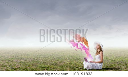 Young lady sitting on green grass with laptop on knees