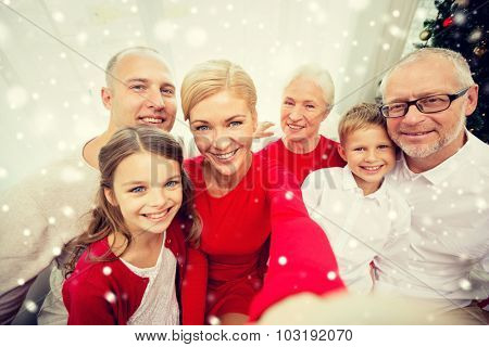 family, holidays, generation, christmas and people concept - smiling family with camera or smartphone taking selfie at home
