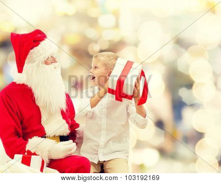 holidays, christmas, childhood and people concept - smiling little boy with santa claus and gifts over lights background