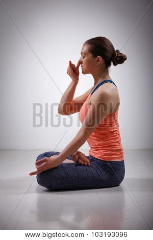 Beautiful sporty fit yogini woman practices pranayama breath control exercise in yoga asana Padmasana - lotus pose with Vishnu mudra in studio