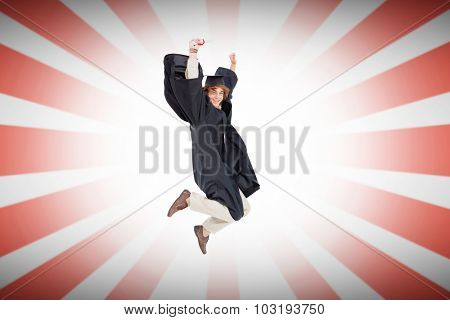 Happy male student in graduate robe jumping against linear design