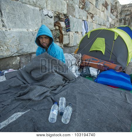 KOS, GREECE - SEP 28, 2015: Unidentified war refugee near tents. More than half are migrants from Syria, but there are refugees from other countries -Afghanistan, Pakistan, Iraq, Iran, Mali, Somalia.