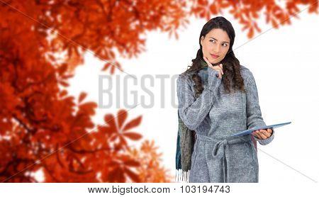Pensive model wearing winter clothes holding her tablet against autumn leaves