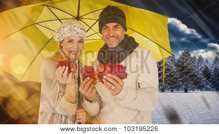 Portrait of couple holding autumn leaves while standing under yellow umbrella against autumn changing to winter