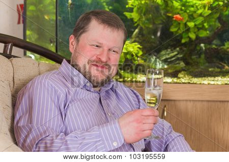 Man sitting in armchair with glass of champaign