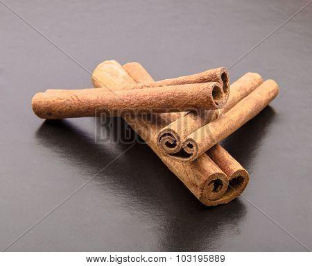 Cinnamon sticks on drak table.