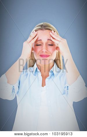Portrait of a blonde getting a headache against blue background
