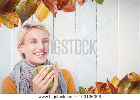 Close up of woman drinking from a cup against autumn leaves pattern