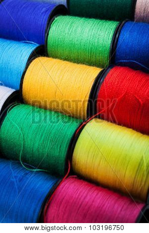colorful threads on spools close up