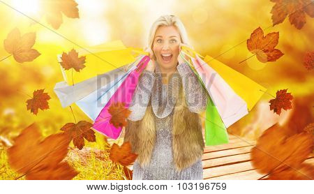 Blonde in winter clothes holding shopping bags against wooden trail across countryside