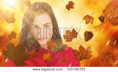 Portrait of a beautiful brunette in red coat against orange abstract light spot design