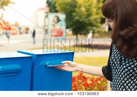 Woman Puts Letters In The Mailbox