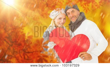 Portrait of happy couple holding heart against walkway along lined trees in the park