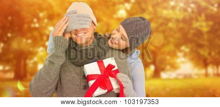 Woman surprising husband with gift against autumn scene