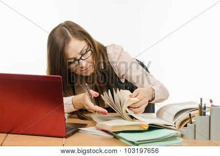 Teacher Leafing Through A Book To Find Information