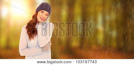 Pretty redhead in warm clothing against autumn scene