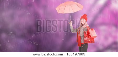 Festive blonde holding umbrella and bags against colourful forest