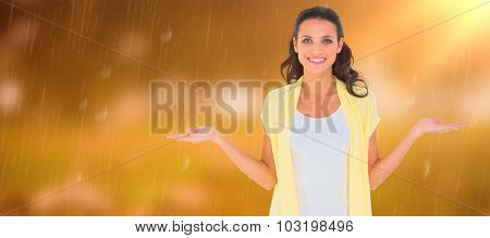 Pretty brunette presenting with hands against autumn scene