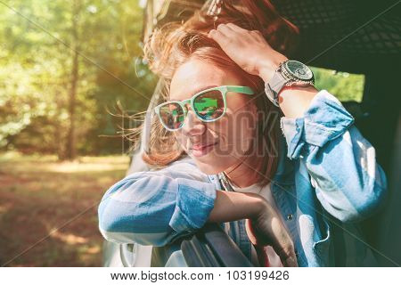 Happy young woman looking through the window car