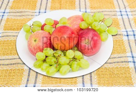 Several Apples, Nectarines And Grape On A White Dish
