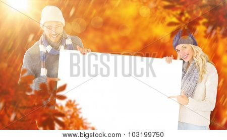 Attractive couple in winter fashion showing poster against autumn scene