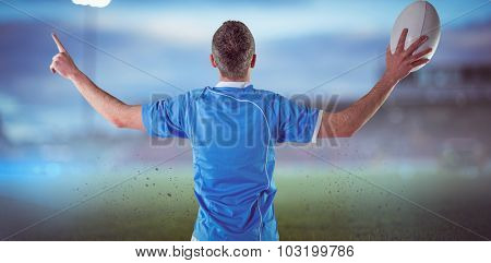 Rugby player gesturing with hands against pitch