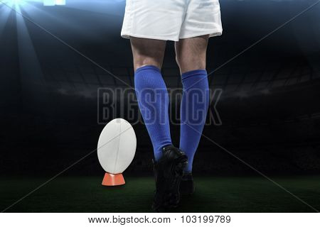 Low section of rugby player going to kick the ball against rugby stadium