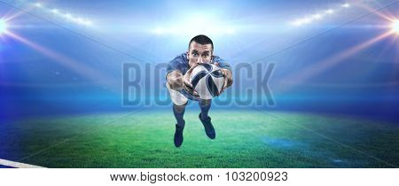 Portrait full length of American football player diving against rugby stadium