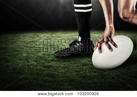 Low section of athlete holding ball while running against rugby stadium