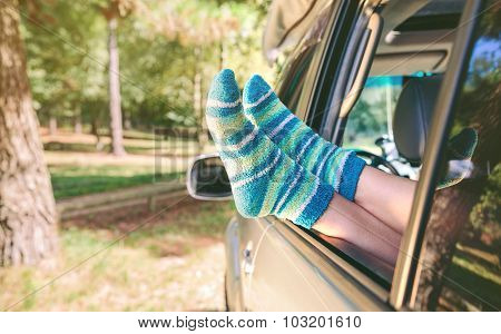 Female legs with socks resting over open window car