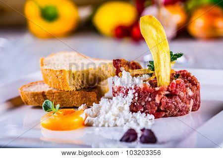 Tasty Steak tartare. Classic steak tartare on white plate with egg bread and cup red wine