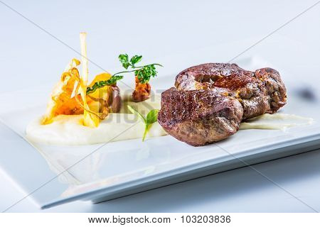 Close up Tender Grilled Beef Meat on White Plate with vegetable decoration.