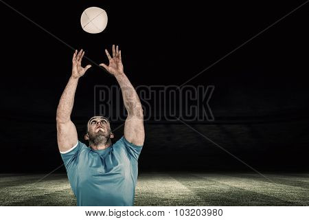 Rugby player catching the ball against football pitch at night