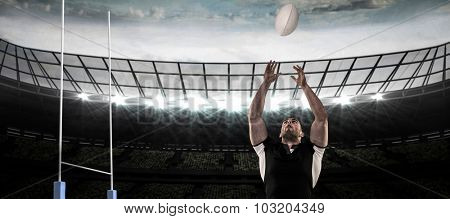 Rugby player catching the ball against rugby pitch