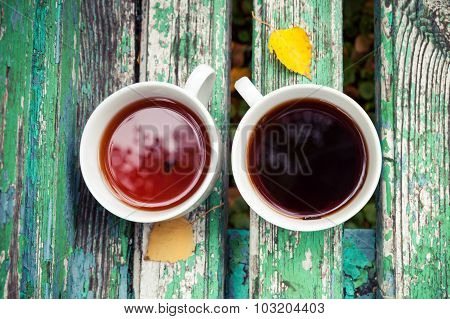 Two Cups Of Tea Is On Old Green Wooden Bench