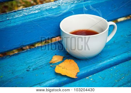 White Cup Of Tea Is On Old Blue Wooden Bench