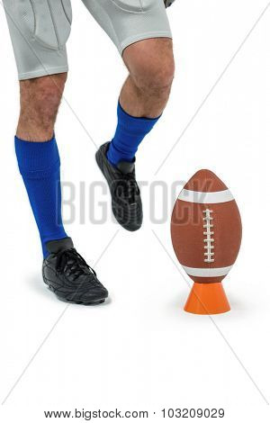 Low section of sports player being about to kick ball against white background