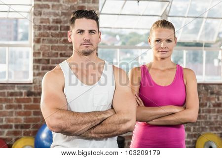 Fit couple face to the camera in crossfit gym
