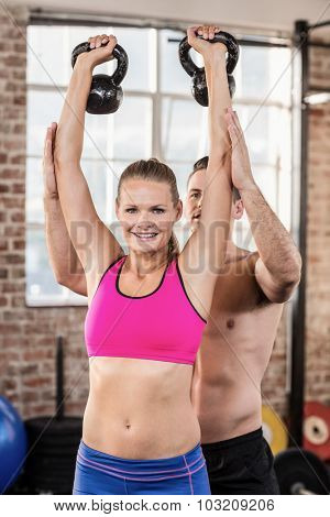 Attentive muscular trainer show how to lift kettlebells in crossfit gym