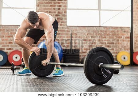 Muscular man set up his barbell weight in crossfit gym