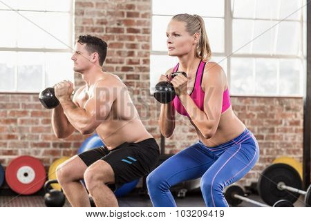 muscular serious couple with kettlebells in crossfit gym
