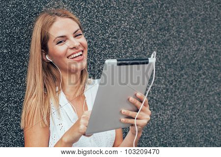 Young Woman Listening To Music On The Digital Tablet