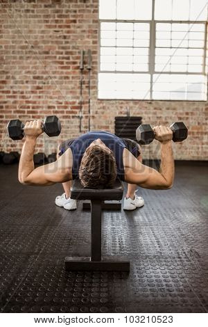 Man doing exercise with dumbbells while lying on bench at the gym