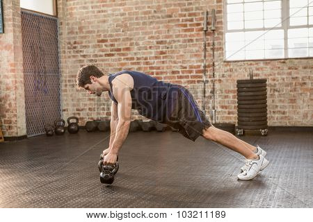 Man doing push up holding kettlebell at gym