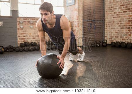 Man doing push ups on medicine ball at the gym