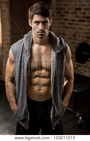 Portrait of a muscular man wearing hood at the gym