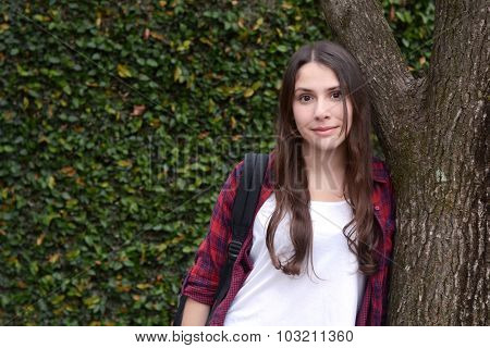 Young Stylish Student Standing Against A Tree