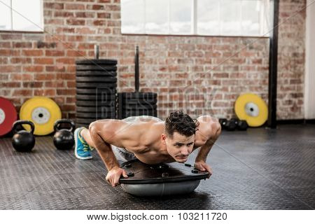 Shirtless man doing bosu push ups at the gym
