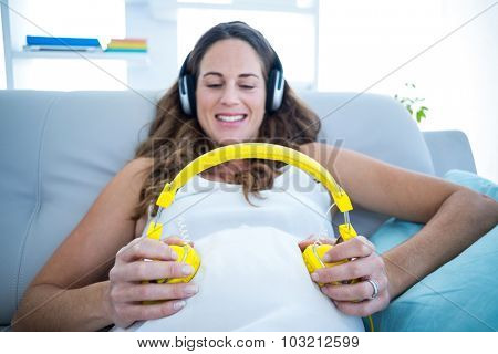 Pregnant woman holding headphones on belly and listening to music in living room