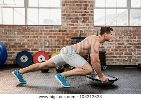 Shirtless man doing exercise with bosu at the gym